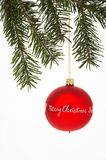 Red Christmas Tree Ball with spruce - rote Weihnachtskugel mit T. Red Christmas Tree Ball with merry Christmas on it hangs on a spruce - rote Weihnachtskugel mit Royalty Free Stock Photography
