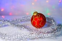 Red Christmas-tree ball and tinsel Stock Photography