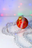 Red Christmas-tree ball and tinsel Stock Photo