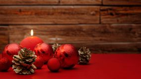 Red christmas tree balls and a red round burning candle on a red table. Red christmas tree balls, golden fir cones and a red round burning candle lying on a stock photography
