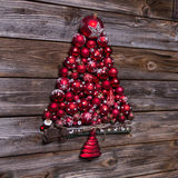 Red christmas tree of balls on wooden vintage background. Stock Photography