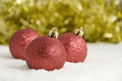 Red Christmas Tree Decorations and Gold Tinsel in Snow Stock Photos