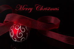 Red Christmas. Red and white Christmas ball with a red ribbon on black Royalty Free Stock Photo
