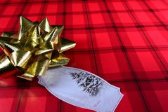 Red Christmas wrapping paper with tag and gold bow. view 3 Stock Photography