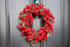 Red Christmas Wreath. A red Christmas wreath hanging on a gray door Royalty Free Stock Image