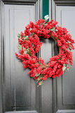 Red Christmas Wreath. A large red holly Chtistmas wreath hanging on a gray door Stock Photo