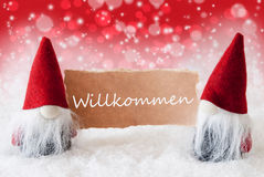 Red Christmassy Gnomes With Card, Willkommen Means Welcome. Christmas Greeting Card With Two Red Gnomes. Sparkling Bokeh And Christmassy Background With Snow royalty free stock photos