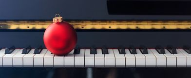 Red Chritmas ball on piano keyboard, front view Stock Images
