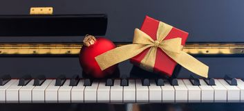 Red Chritmas ball and gift box on piano keyboard, front view. Red Chritmas ball and gift box with golden bow on classical piano keyboard, front view Royalty Free Stock Photography