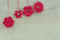 Red chrochet flowers as christmas decoration. On wooden background Stock Photo