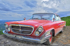 Red Chrysler 300. A classic vintage red Chrysler 300 on display with a colorful background of sky and mountains royalty free stock images