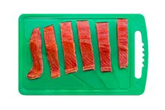 Red chum salmon fish cut into pieces on a green chopping board stock images