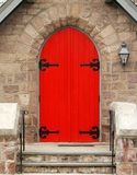 Red Church Door. A bright red door set against an old stone church royalty free stock images