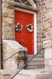 Red Church Door with Holiday Decoration. Red Church Door with Holiday Wreath Decoration Royalty Free Stock Photography