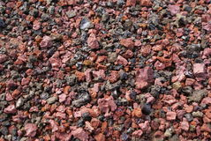Red cinders. Close up of red, black green and beige cinders on the ground Stock Photo