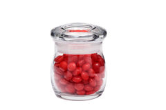 Red Cinnamon Candy in Jar. Many pieces of red cinnamon candy in a small jar isolated on a white background great for use alone or in composites stock photo