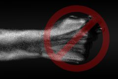 The red circle crosses out a hand that shows a fig, a sign of prohibition, disagreement, refusal, on a dark background. Horizontal frame royalty free stock image
