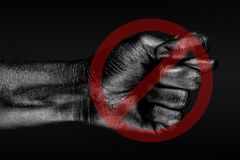 The red circle crosses out a hand that shows a fig, a sign of prohibition, disagreement, refusal, on a dark background. Horizontal frame stock photos