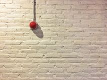 Red circle fire alarm on vintage white brick wall. royalty free stock image