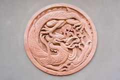 Red circular dragon bas-relief on a grey wall. China Royalty Free Stock Photo