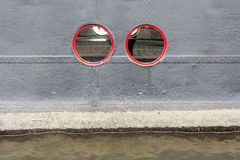 Red circular windows on the black cruise ship. Moored on the waterfront Royalty Free Stock Photography
