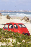 Red Citroen 2CV on a Beach. French red Citroen 2 cv isolated on a beach. This car whas built for to get chicken eggs from farm to market in one piece because of royalty free stock photos