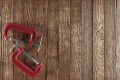 Red clamp on the old  wooden background Royalty Free Stock Photos