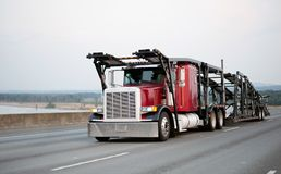 Red classic big rig semi truck with car hauler trailer running b Stock Photos