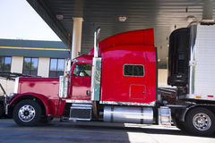 Red classic big rig semi truck and reefer trailer Royalty Free Stock Photography