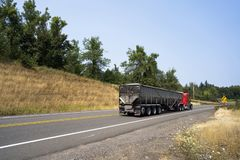 Red classic big rig semi truck transporting cargo in long covered bulk trailer. Popular American classic hoody big rig semi trucks with chrome accessories embody royalty free stock photography