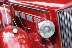 Red Classic Car. A view of the headlight & bonnet of a red classic car Royalty Free Stock Photos
