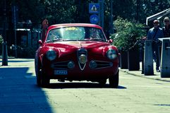Classic Coupe` at Mille Miglia 2016. A red classic coupe` passing through Tasso street Bergamo, Italy before the crowd during the 2016 Mille Miglia classic car Stock Image