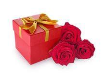 Red classic gift box with golden satin bow and bouquet of roses. Isolated on white background Royalty Free Stock Photo