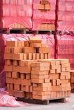 Red clay bricks stacked on pallets Stock Image