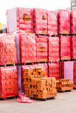 Red clay bricks stacked on pallets Stock Images