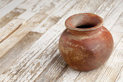 Red clay pot on rustic table Royalty Free Stock Images