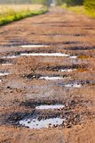 Red clay road with holes. Local red clay road with wet holes surrounded by field and forest on unfocused background Royalty Free Stock Images