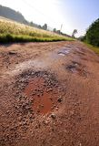 Red clay road with holes. Local red clay road with wet holes surrounded by field and forest. Oblique shoot Royalty Free Stock Image