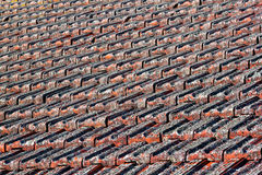 Red Clay Tiled Roof With Lichen. A closeup look at a red clay tiled roof covered in lichen stock photography