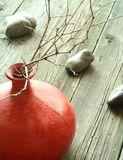 Red clay vase with dry twigs and stones on wooden royalty free stock photography