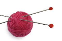 Red clew and two knitting needles Royalty Free Stock Images