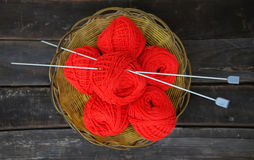 Red clews on wood planks. Basket with some red clews and knitting needles stock photos