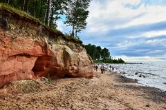 Free Red Cliff On The Beach By The Water Royalty Free Stock Photos - 170906268