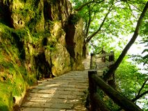 Red cliff plank road near the rocks. A red cliff plank road on the mountain near big mossy rocks in three kingdom studio of wuxi jiangsu province China stock images
