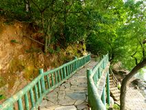 Red cliff plank road near the rocks. A red cliff plank road on the mountain near big mossy rocks in three kingdom studio of wuxi jiangsu province China stock image