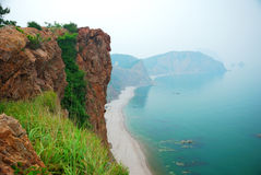 Red cliff at sea shore. Bloody colored cliff standing at sea shore in a foggy morning Royalty Free Stock Photography