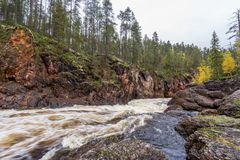 Red cliff, stone wall, forest, waterfall and wild river view in autumn Royalty Free Stock Photos