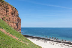 Red cliffs and beach at German island Helgoland royalty free stock photo