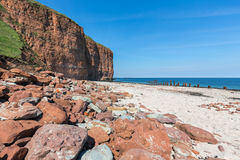 Red cliffs and beach at German island Helgoland. Red cliffs and beach at Helgoland island, Germany royalty free stock photography