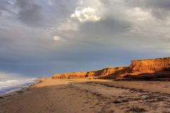 Red Cliffs on Prince Edward Island. The setting sun shines on red sandstone cliffs on the North shore of Prince Edward Island Royalty Free Stock Images